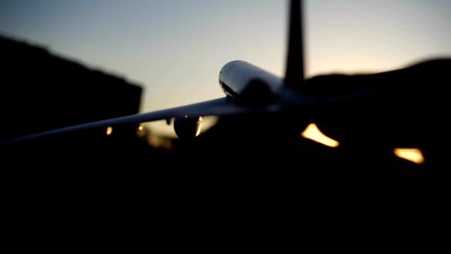 man holding airplane at sunrise