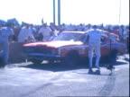 Man holding chalkboard signaling AJ Foyt for pit stop at Riverside 500 Riverside International Raceway / driver AJ Foyt racing Ford Torino Cobra...