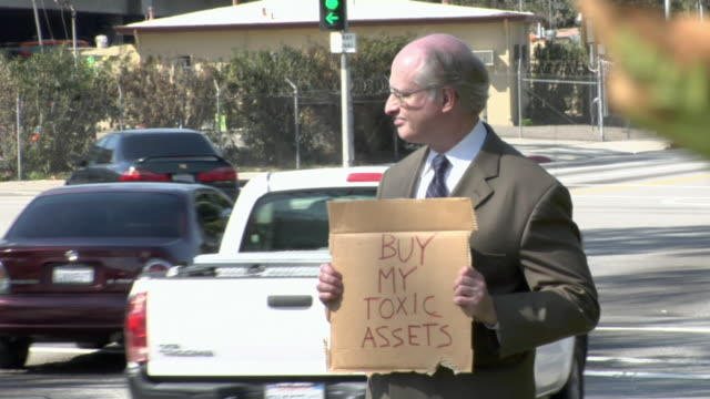 MS ZI ZO Man holding sign saying 'Buy my Toxic Assets' on street, Los Angeles, California, USA