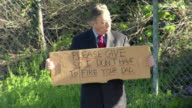 MS Man holding sign saying 'Please Give so I don't Have to Fire Your Dad' on street, Los Angeles, California, USA