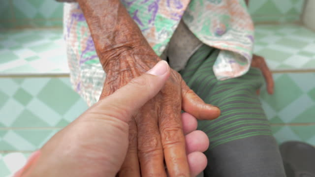 Man holding the hand of the senior woman in his hand