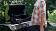 MS TU man holding tongs barbecuing skewered meat at grill in backyard