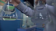 CU Man holding two beakers with liquid, Beijing, China