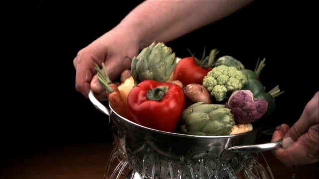 CU, SLO MO, Man holding vegetables in colander, close-up of hands