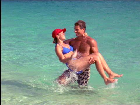 Man holding woman above shallow ocean water / smiling woman splashing water into his hair