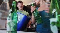 MS Man holds recycling container, woman filling it with glass bottles off of kitchen counter, Hoboken, New Jersey, USA