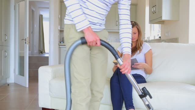 Man hoovering carpet while wife is reading on sofa