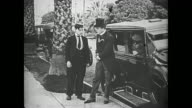 Buster Keaton hops onto the back of a car and, once it comes to a stop, opens the door for the passengers hoping for a tip