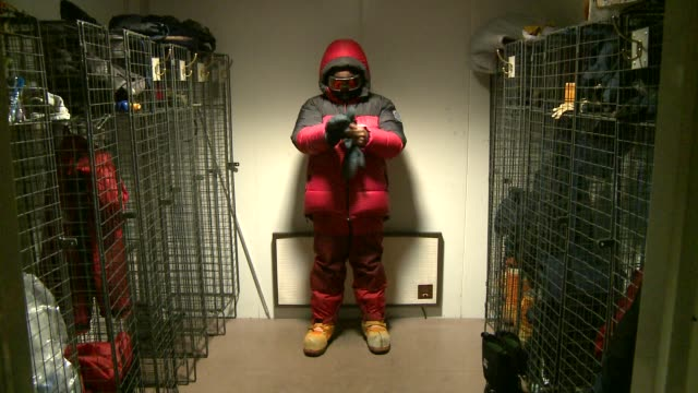 A man in a full snowsuit and mask stands in a dressing room and pulls on a pair of gloves. Available in HD.