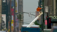 A man in a high reach paints a street pole on 34th street in New York City's shopping district.