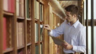 TU Man in a library searching for a book with a tablet
