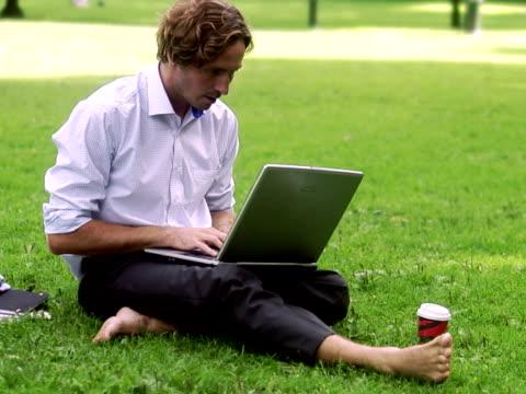 A man in a park using a laptop Sweden.