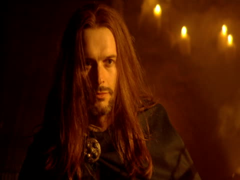 A man in a robe with long hair sits in a candlelit room.