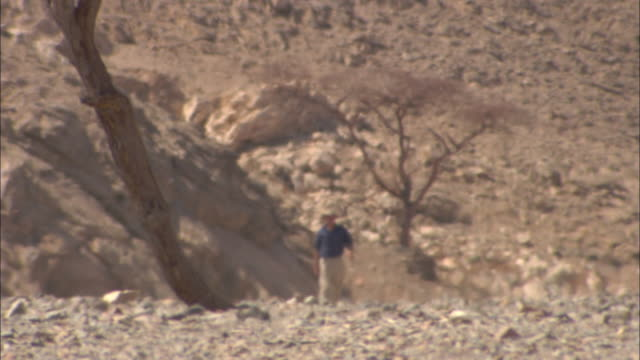 A man in a rocky desert hikes through a heat wave in Sikait, Egypt.