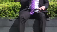 A man in a suit talks into a mobile phone whilst balancing a tablet computer on his lap and sitting in the sunshine, London, UK.