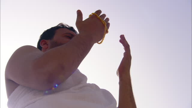 A man in a white robe holds beads while he prays.