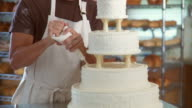 TU Man in bakery decorating wedding cake and smiling at camera / racks of bread in background