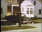 1951 PAN man in black Ford pulling into driveway in suburban home / son runs to greet him / Detroit