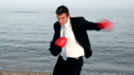 Man in black suit fights at the beach