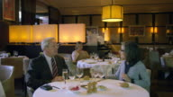 WS man in business suit and woman at table in restaurant being served food