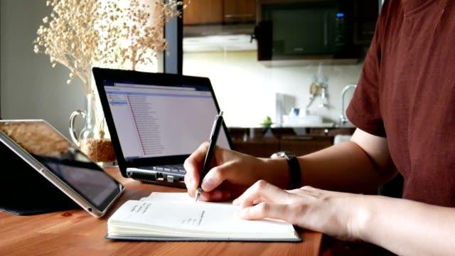 Mann in Freizeitkleidung schreiben auf Notebook am Wohnzimmertisch - home-Office oder in Heimarbeit Konzept
