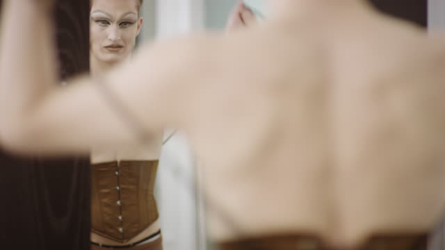 Man in drag putting on corset