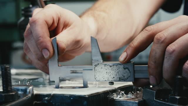 Mensch in der Fabrik Maßnahme Loch aus Stahl mit Vernier Bremssattel.