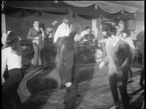 B/W 1965 man in fez dancing in nightclub with woman as band plays on stage in background / newsreel