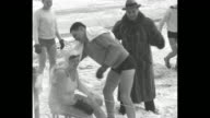 Man in fur coat leads wintertime bathers in calisthenics on snowcovered shore of Lake Michigan bathers wear longsleeved shirts over bathing suits /...