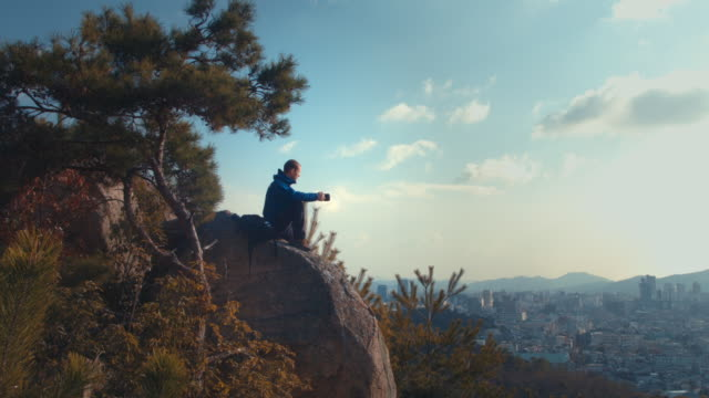A man in his 30's hiking and looking out over the city