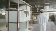 WS TS man in lab coat and hard hat walking along multi-story warehouse in furniture production, rear view