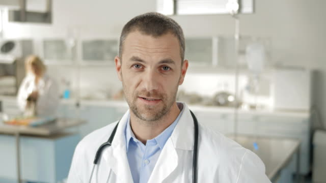 Man In Lab Coat Talking At Camera