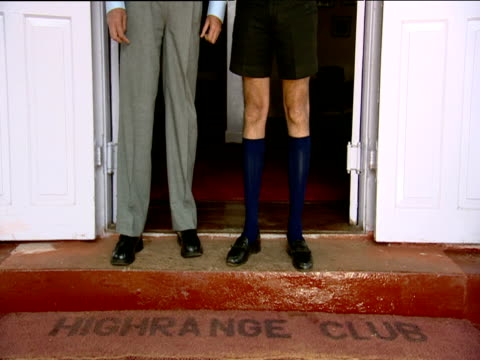Man in long trousers stands next to man in short trousers and long socks in doorway of clubhouse Munnar India