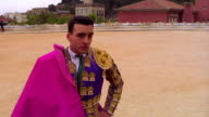 PORTRAIT man in matador uniform with cape turns head toward camera in arena / Spain