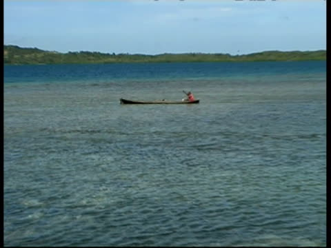 Man in paddling a canoe in sea, MS, Panama, Central America
