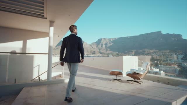 Man in penthouse kijkt uit over de stad