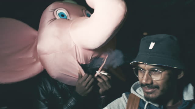 Man in plush head of college mascot smoking outdoors at night
