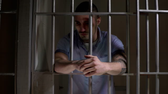 4K DOLLY: Man in Prison Jail Cell leaning on the bars