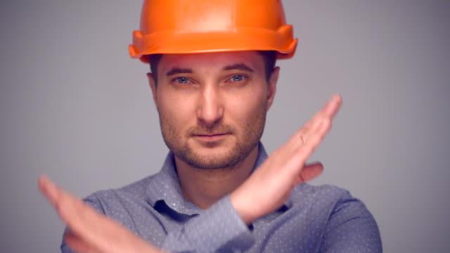 Man in protective helmet gesturing stop sign