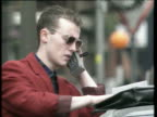 Man in red jacket talking on large mobile phone leaning on car zoom out to show motorbikes parked in foreground; 1980s