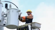MS LA  Man in Saftey Gear Attaching Power Line to Transformer Box / Oyster, Virginia, USA