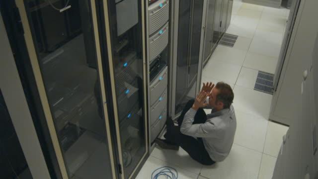 WS Man in server room sitting on floor, reeling back on floor, Sydney, Australia