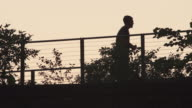 A man in silhouette stops on the highline to take a picture.  Slow Motion