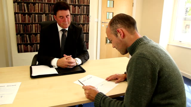Man in solicitors signing Divorce papers