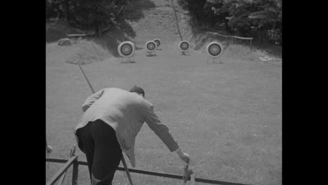 Man in sports jacket and tie shoots bow and arrow at targets on range