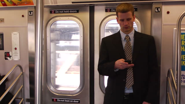 man in suit on subway using his phone