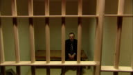 MS Man in suit sitting in prison cell and putting head in hands/ New Jersey