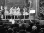B/W 1914 man in top hat performing as chorus line dances in theater