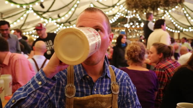 CU Man in traditional dress drinking from beer jug at traditional Oktoberfest inside tent / Munich, Bavaria, Germany