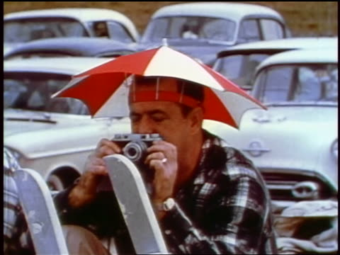 1957 man in umbrella hat taking picture with camera outdoors / feature